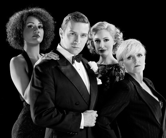 A black and white promotional image for Chicago the musical. Tupele Dorgu, Stefan Booth, Ali Bastian and Bernie Nolan are all dressed smartly and smouldering at the camera.