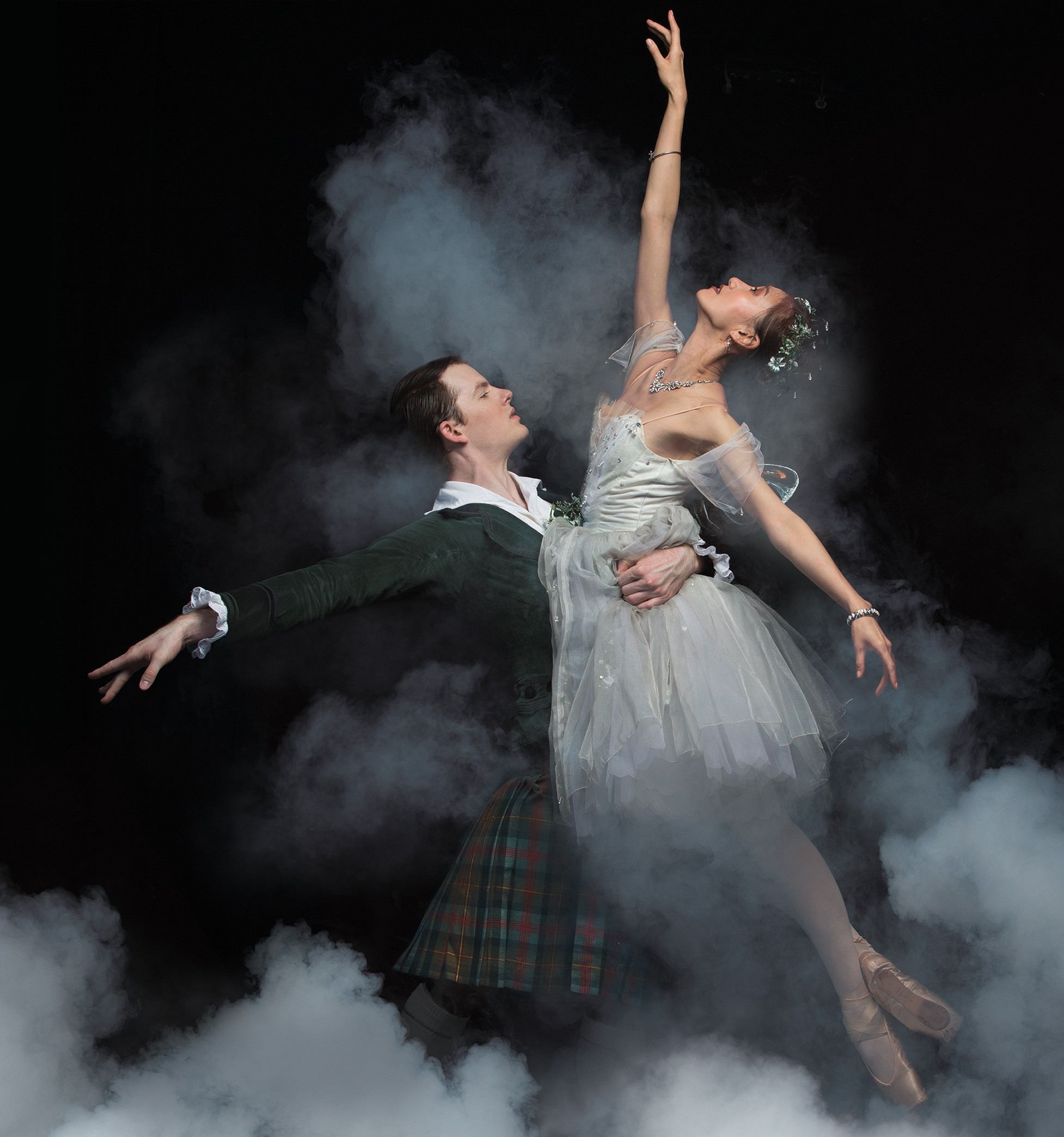 Queensland Ballet's La Sylphide. Promotional image shows Scottish James with his arm around the waist of the delicate, winged Sylphide. They are surrounded by smoke.