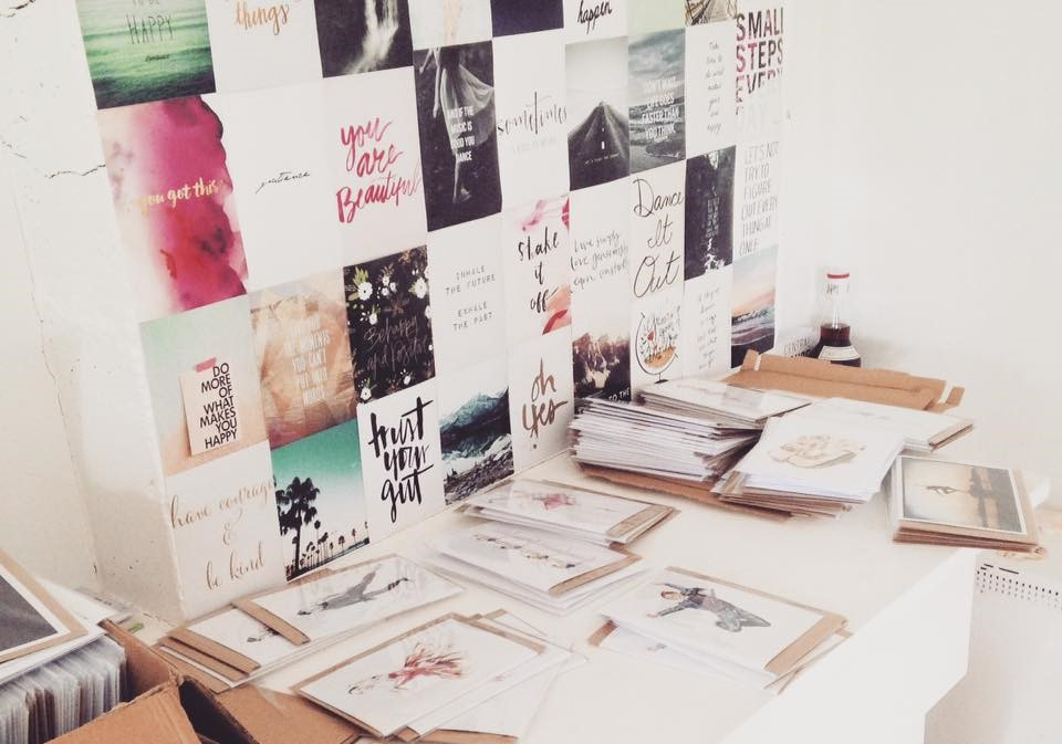 One of Olivia's creative art spaces is a long desk in front of a wall covered in postcards that have inspiring and motivating quotations written on them.