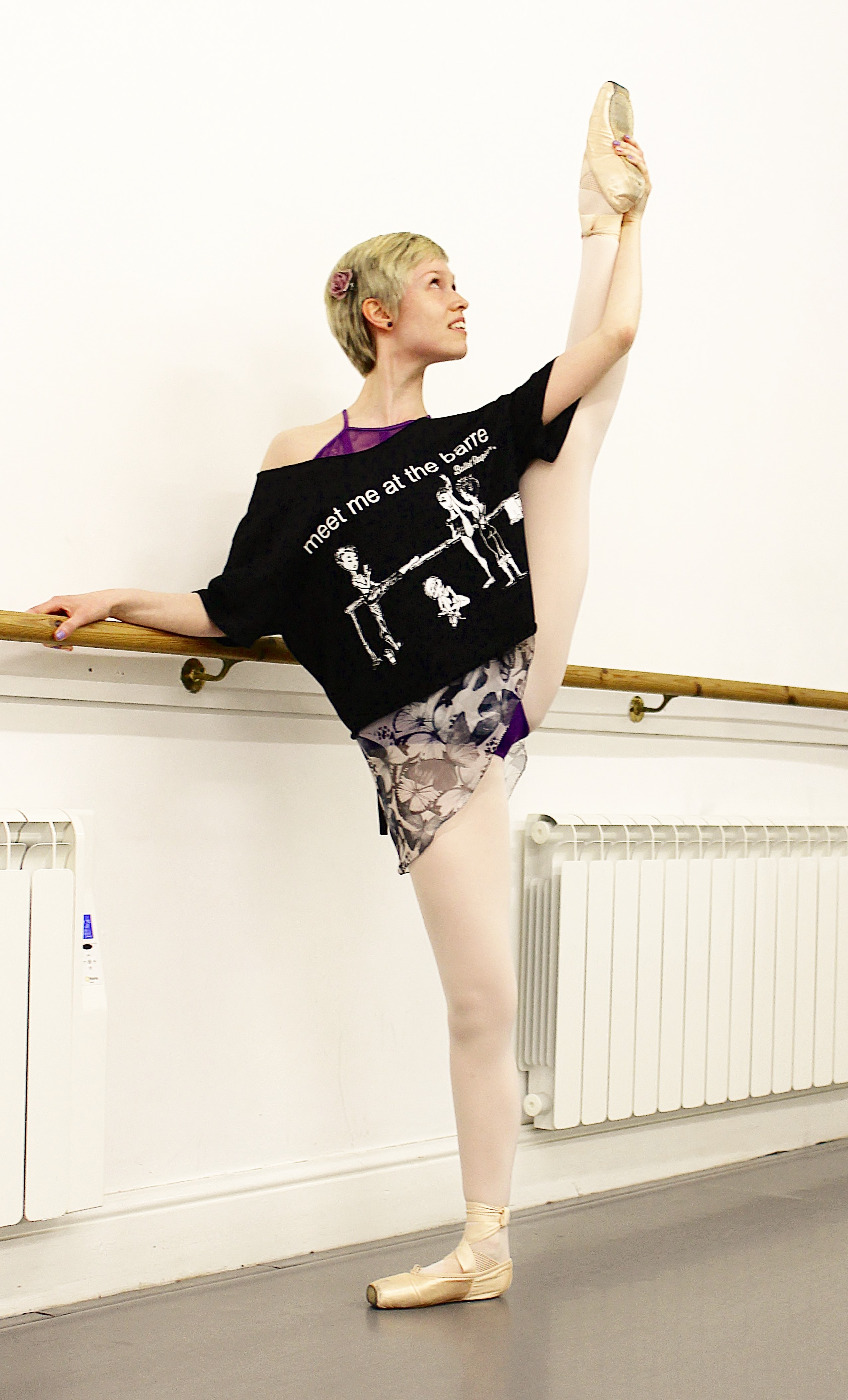 Georgina Butler wearing the black 'Meet Me At The Barre' T-shirt by Ballet Papier. Georgina is wearing the T-shirt over her ballet practice leotard and skirt. She is standing at a ballet barre in a dance studio, with her right hand gently resting on the barre and pointe shoes on her feet. Her left leg is stretched out to the side, high in the air, in a développé à la seconde.