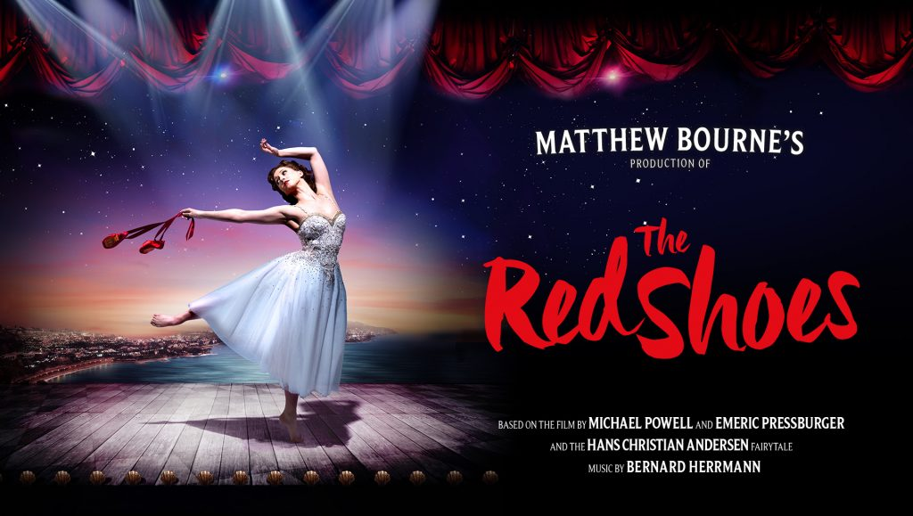 Matthew Bourne's production of The Red Shoes. Promotional image showing Ashley Shaw as Victoria Page. She is standing under a spotlight and holding a pair of red pointe shoes.
