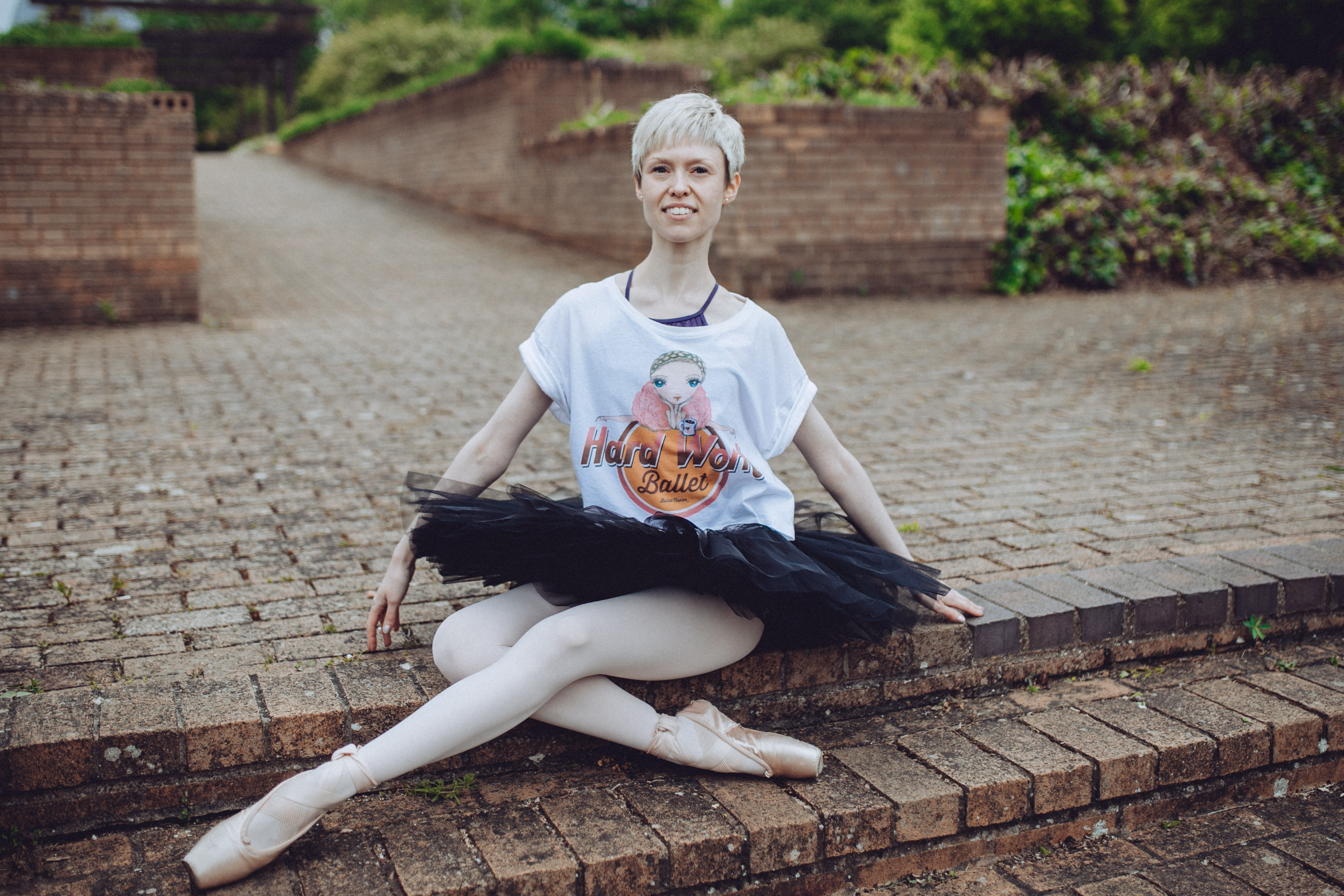 Georgina Butler wearing the 'Hard Work Ballet' T-shirt by Ballet Papier. Georgina is wearing the T-shirt over a purple leotard and with a black tutu and pointe shoes.