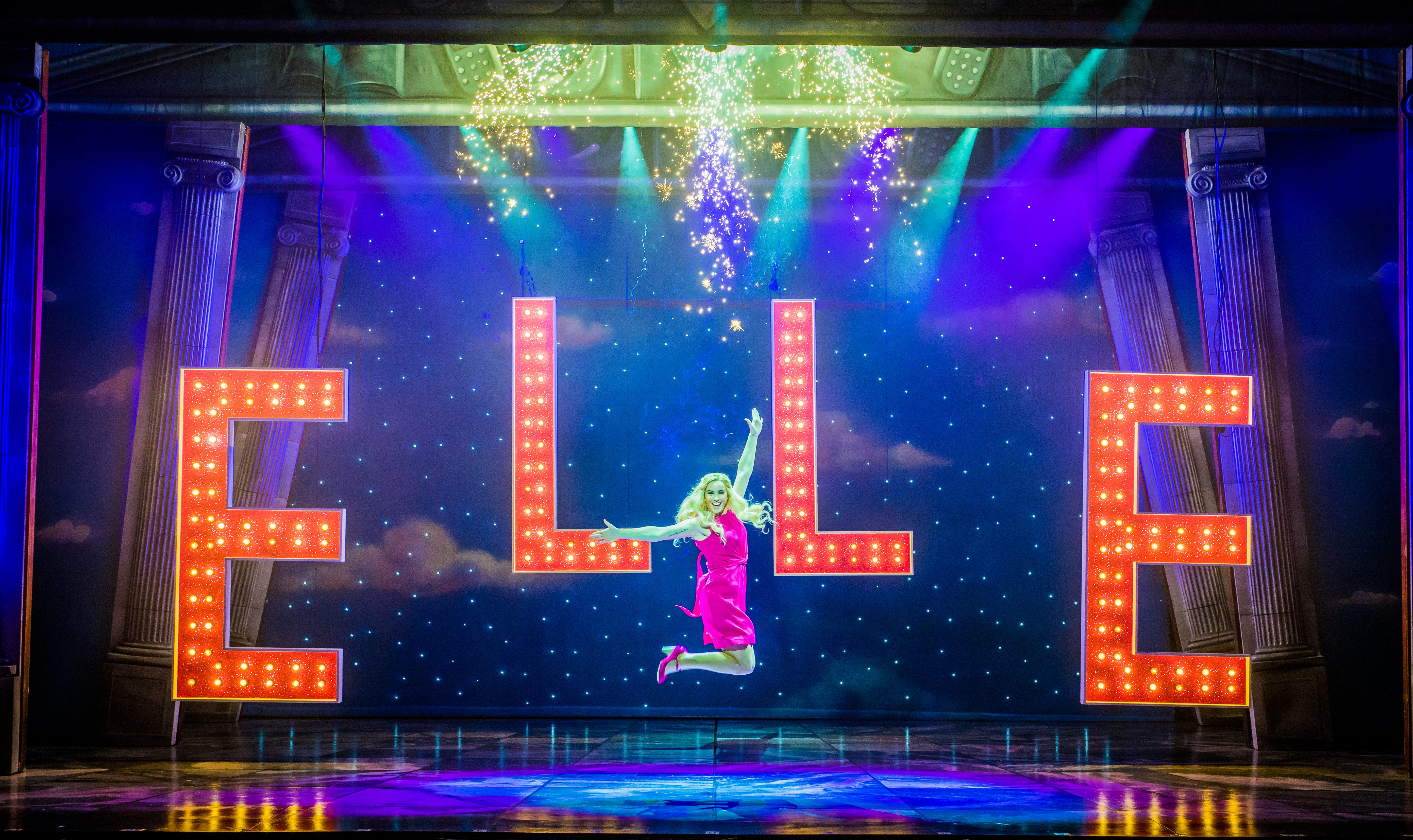 """Lucie Jones as Elle Woods in Legally Blonde the musical. She is wearing a pink dress and jumping in the air, in front of huge, brightly lit red letters spelling out """"Elle""""."""