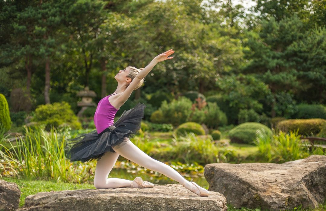 Georgina Butler photographed outside in a tranquil garden, during a classical ballet photo shoot. She is sideways on to the viewer, in a kneeling swan pose, with an arched back and her gaze directed up to the sky.