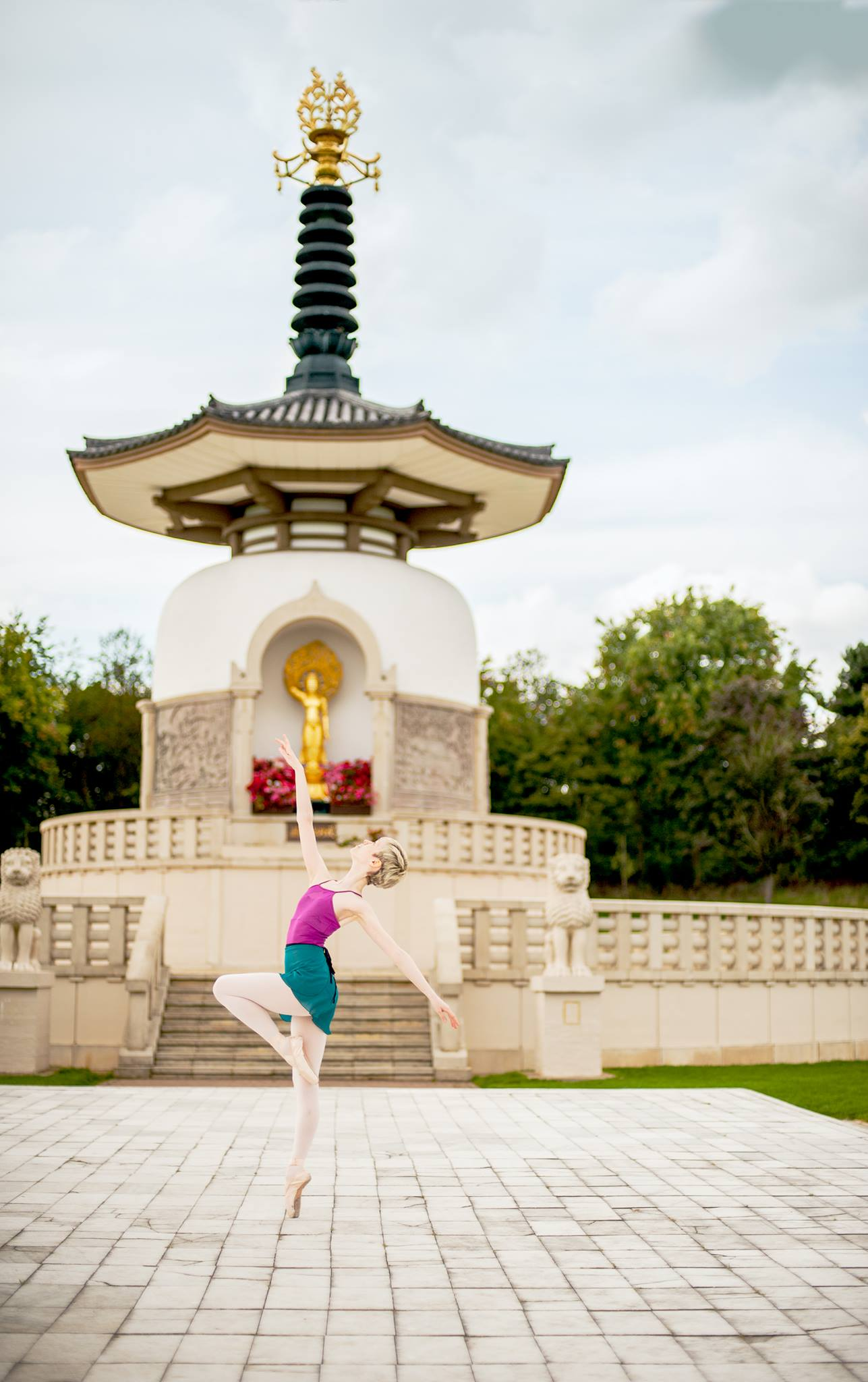 Georgina Butler. International Dance Day 2019. Dance and Spirituality. Georgina Butler wearing a pink leotard and turquoise skirt, dancing en pointe in front a Peace Pagoda.