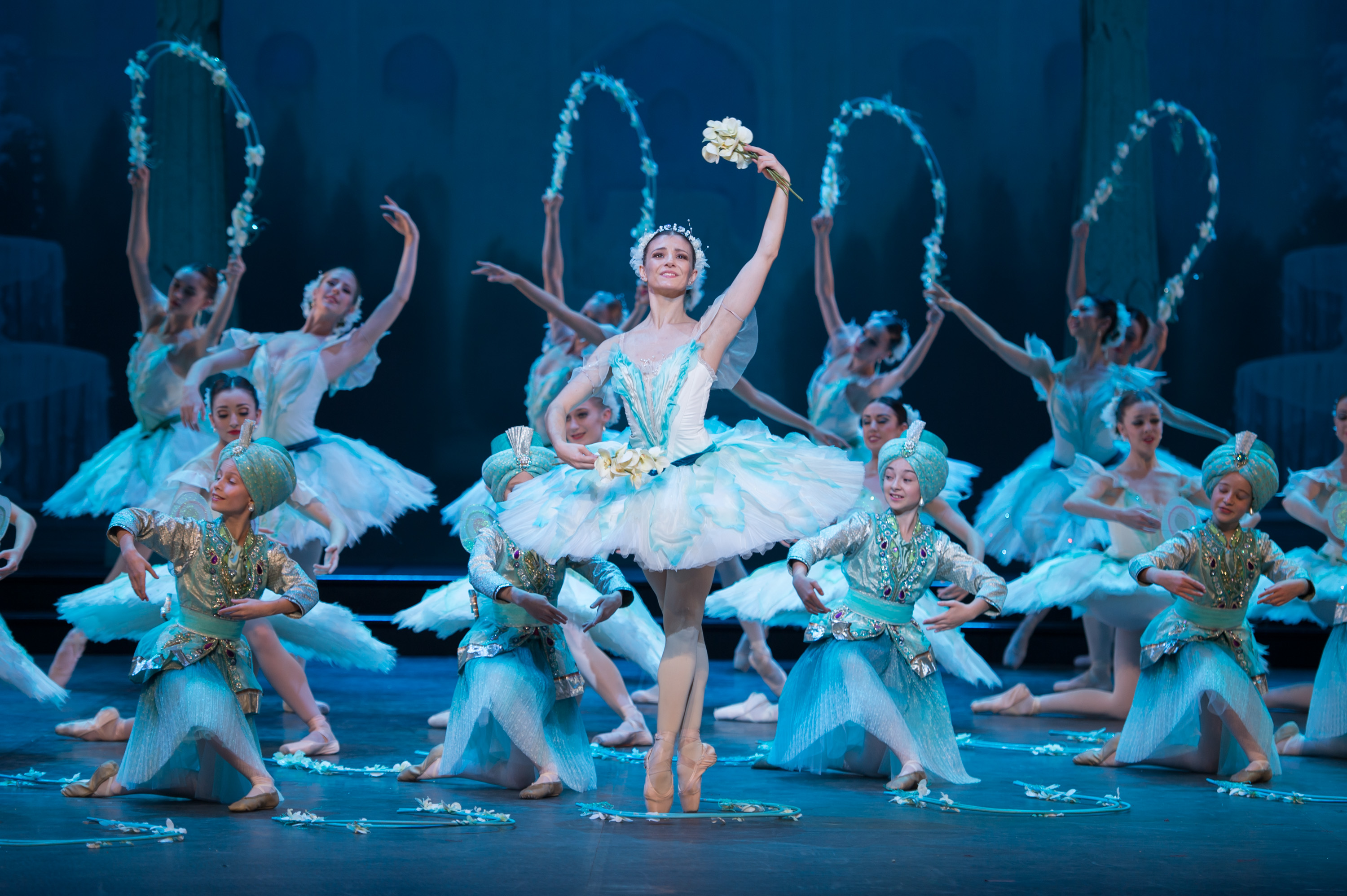 English National Ballet performing the world premiere of Le Corsaire. Alina Cojocaru standing en pointe centre stage, dressed in a white and mint green tutu costume, with artists of English National Ballet holding garlands of flowers in the background.