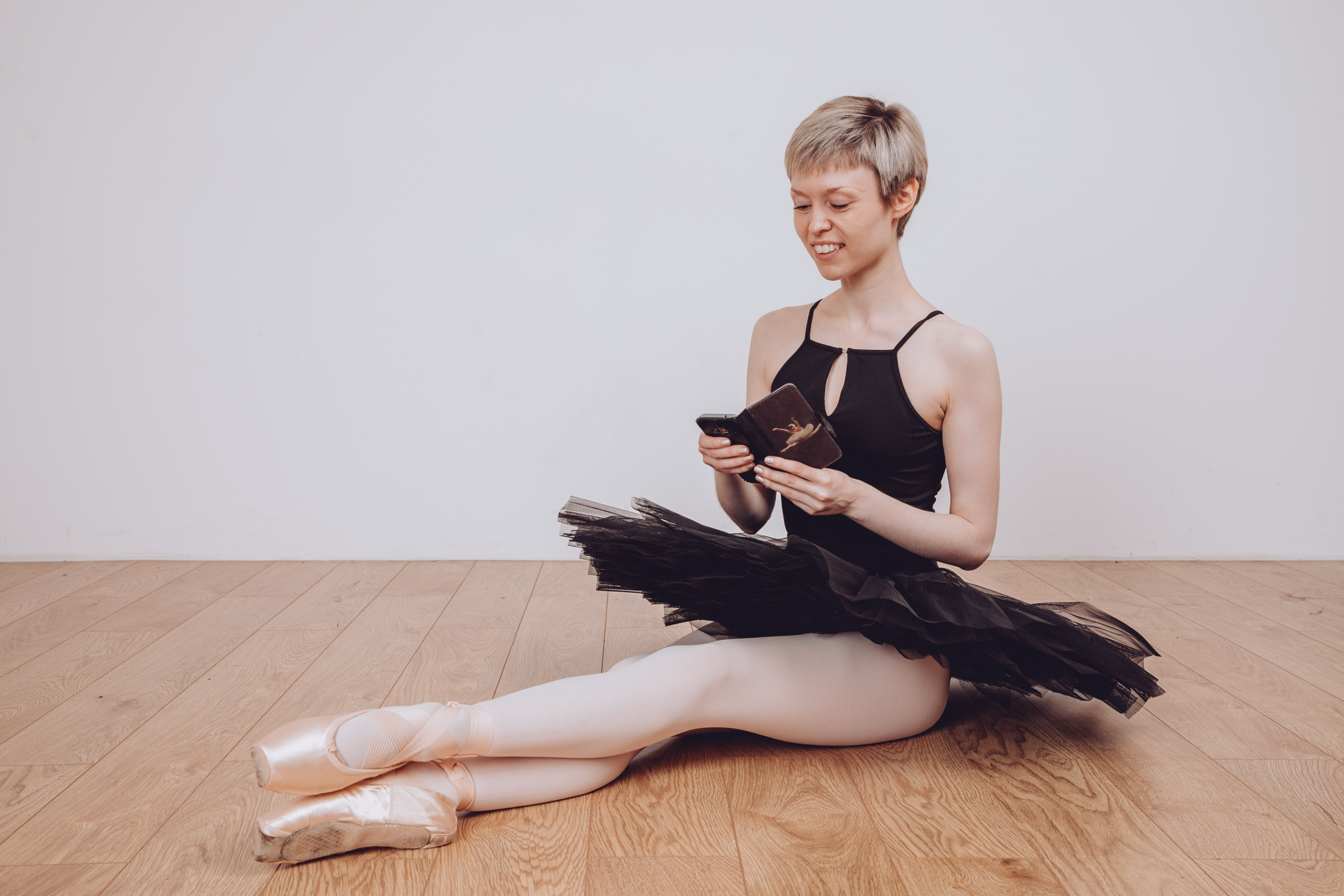 World Ballet Day 2019. Georgina Butler – wearing a black leotard, tutu and pointe shoes – sitting on the floor looking at her phone, ready to watch the annual online celebration of ballet.