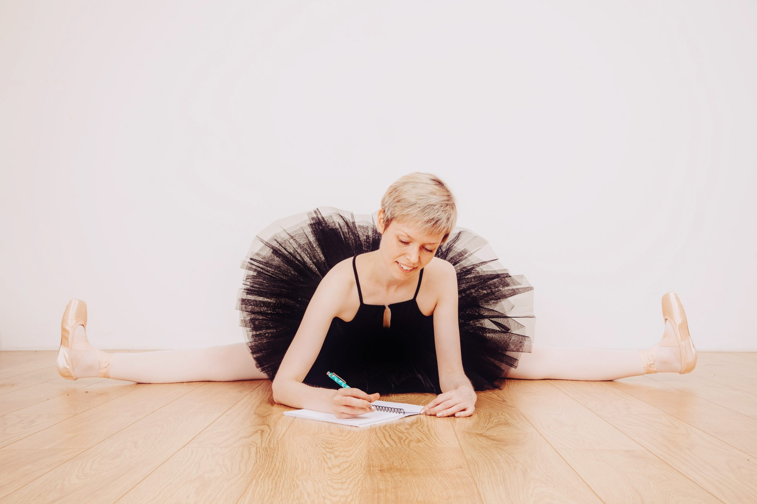 International Dance Day 2020. Georgina Butler writing while sitting in the splits.