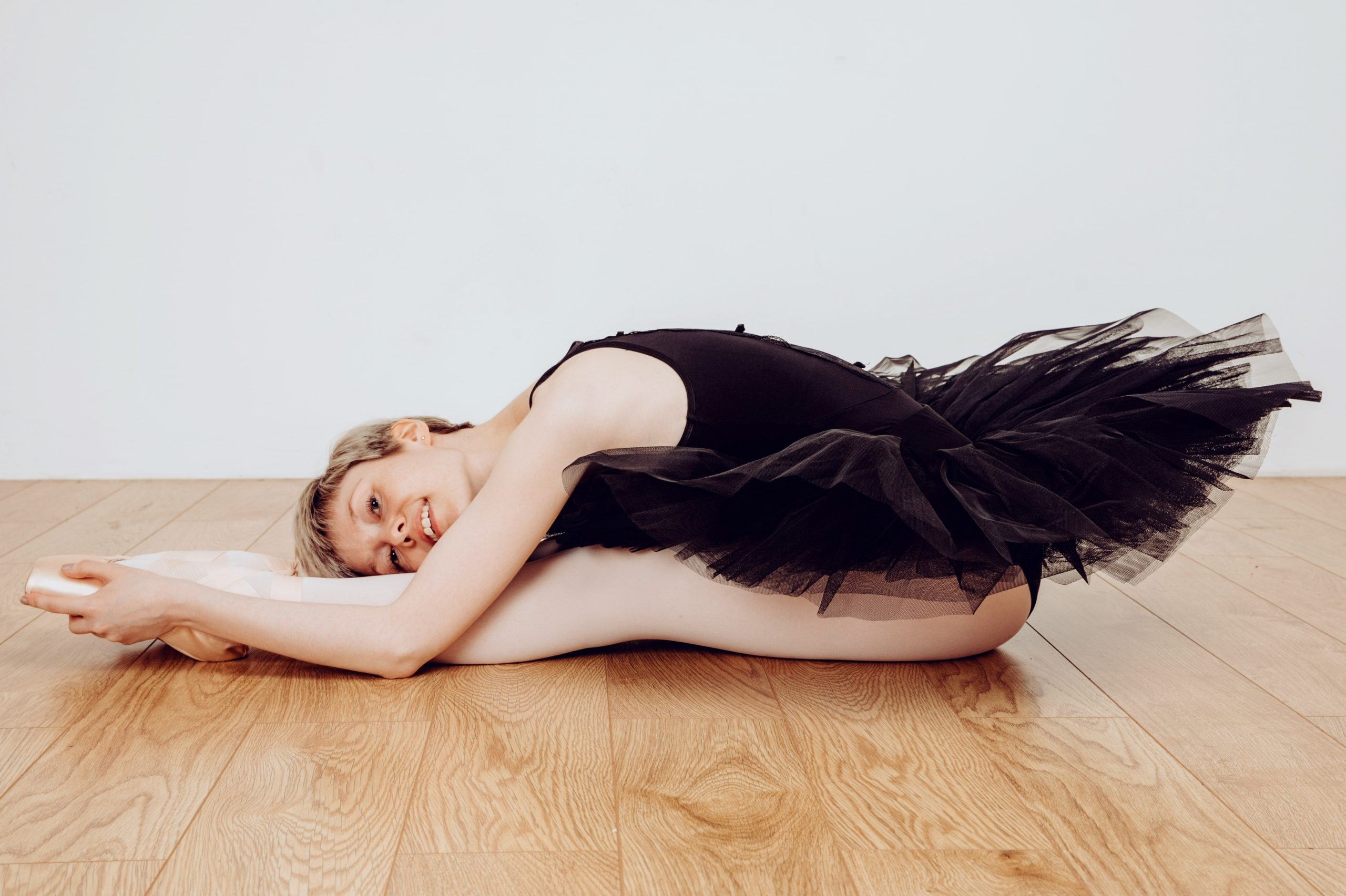 Georgina Butler photographed sitting on a wooden floor. She is effortlessly leaning her torso forward to rest on her legs, which are stretched out in front of her. She is wearing a black leotard, black tutu, pink ballet tights and pink ballet shoes. She is looking directly at the viewer and smiling.
