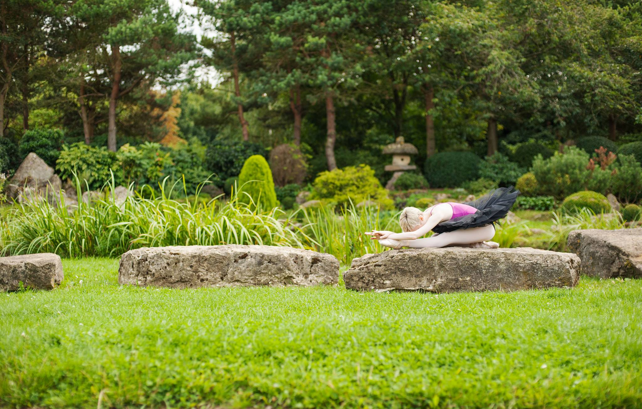 Georgina Butler, wearing a pink leotard and black tutu, resting in an elegant ballet pose on a large flat rock in an idyllic garden. Photo by Terry Grehan.