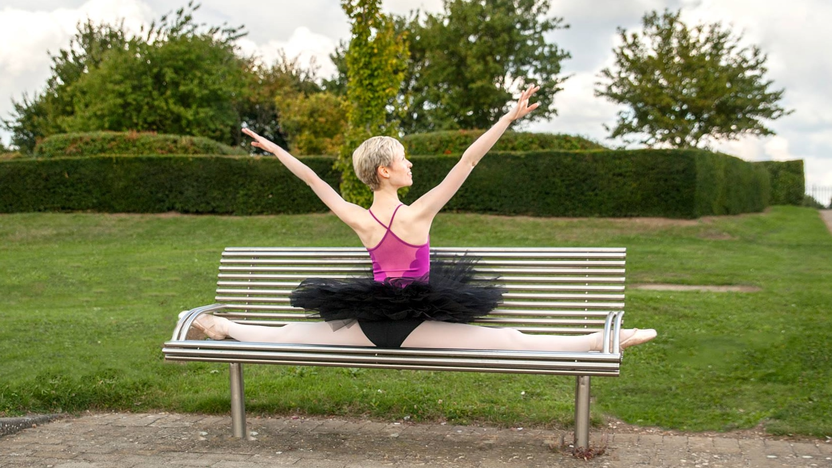 Georgina Butler, wearing a pink leotard and black tutu, sitting on a bench with her back to the viewer. Her legs are in the box splits and her arms are reaching above her head in a wide 'v' shape. Photo by Terry Grehan.