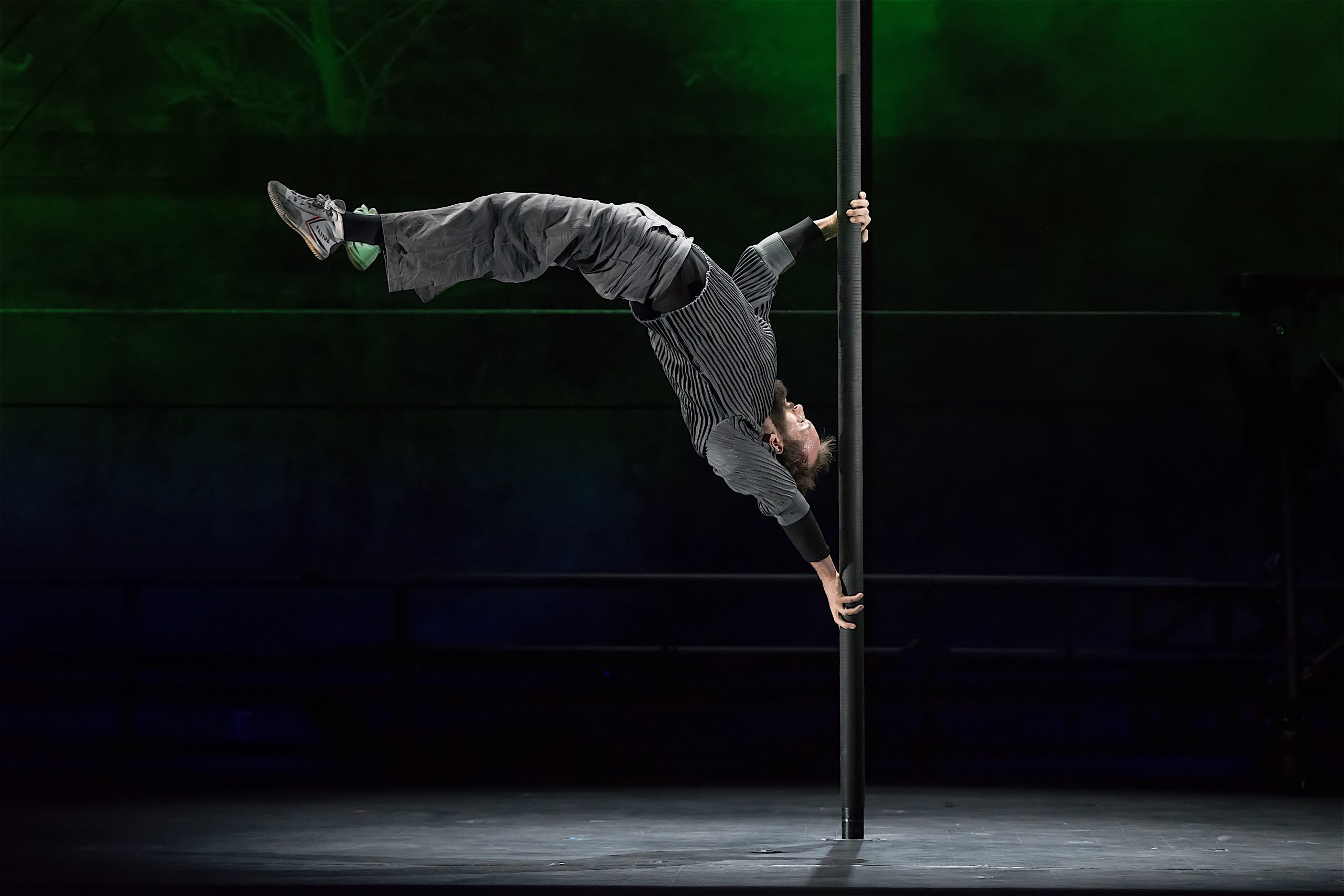 The 7 Fingers performs Passagers. A male circus artist demonstrates his strength and flexibility as he strikes a pose horizontally, mid-backflip, with both hands holding onto a vertical pole.