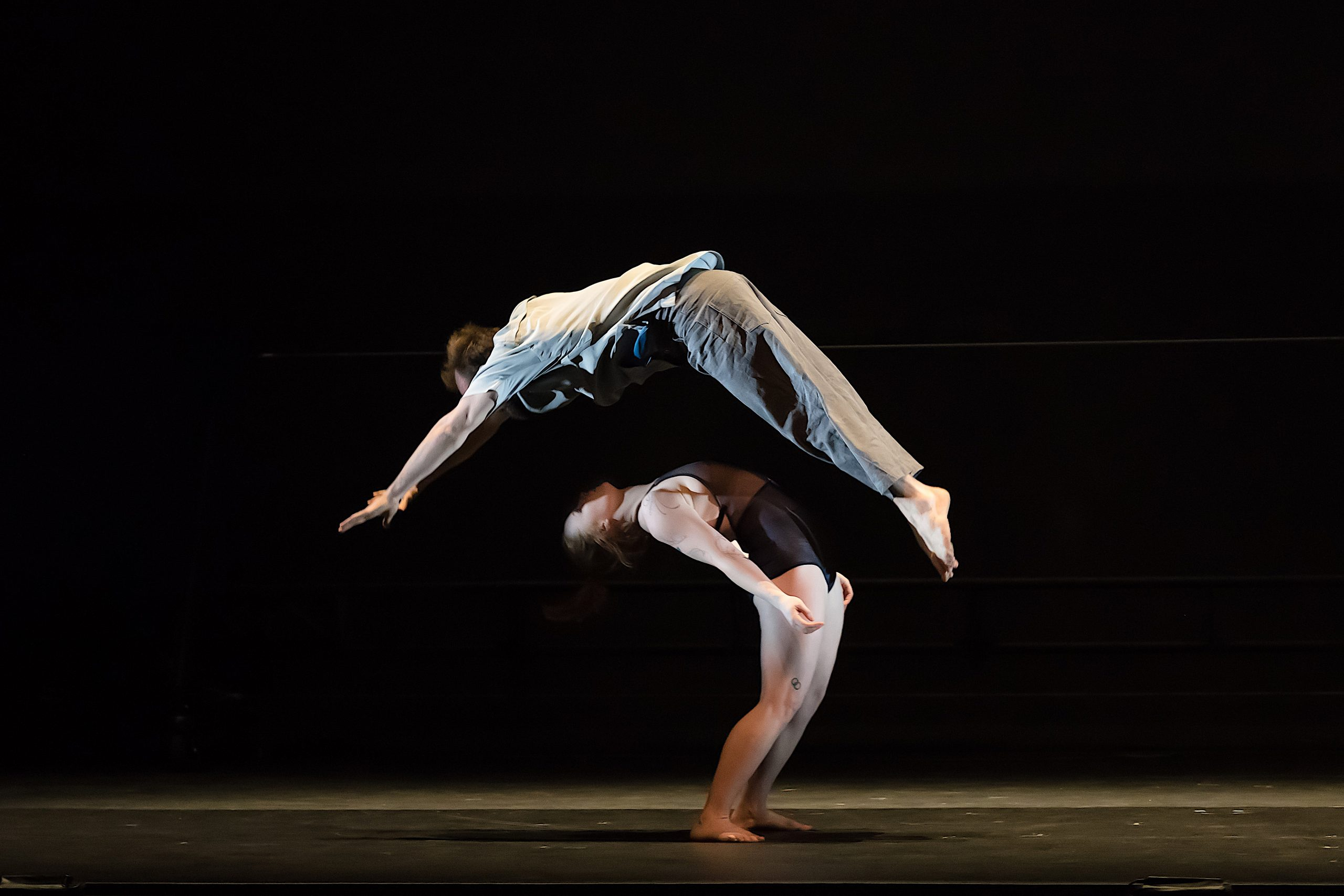 The 7 Fingers performs Passagers. A standing circus artist leans into a deep backbend as a second circus artist soars above to tumble over her.