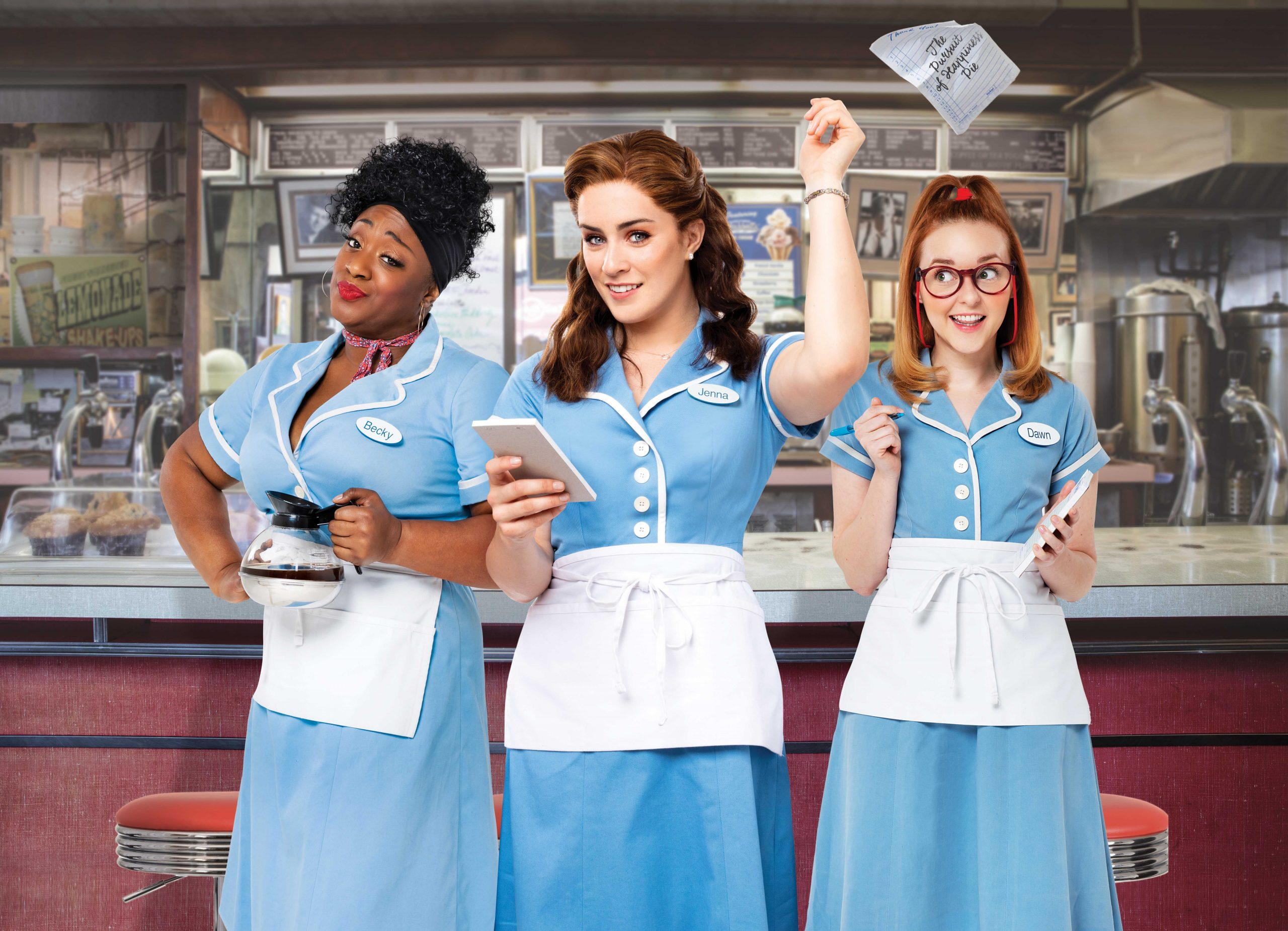 Waitress UK Tour promotional image. Lucie Jones as Jenna, Sandra Marvin as Becky and Evelyn Hoskins as Dawn. All three women are wearing a waitress uniform comprising a pale blue dress with white buttons and a white apron.