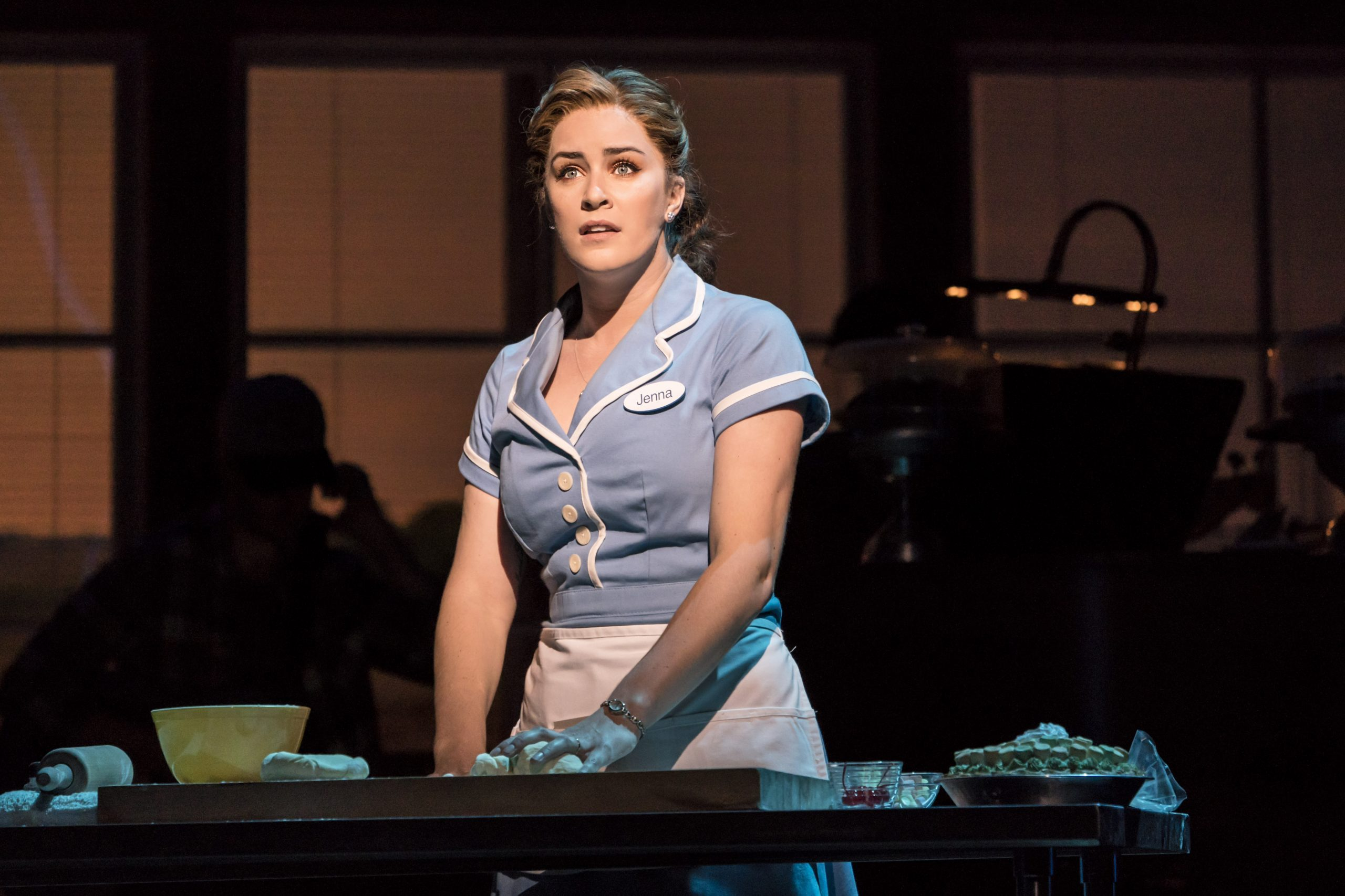 Lucie Jones as Jenna in Waitress. She is wearing a waitress uniform comprising a pale blue dress with white buttons and a white apron. Stood at a table, she is kneading pastry with a wistful expression on her face.